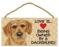 Skilt i træ: Love is Being Owned By A Dachshund.